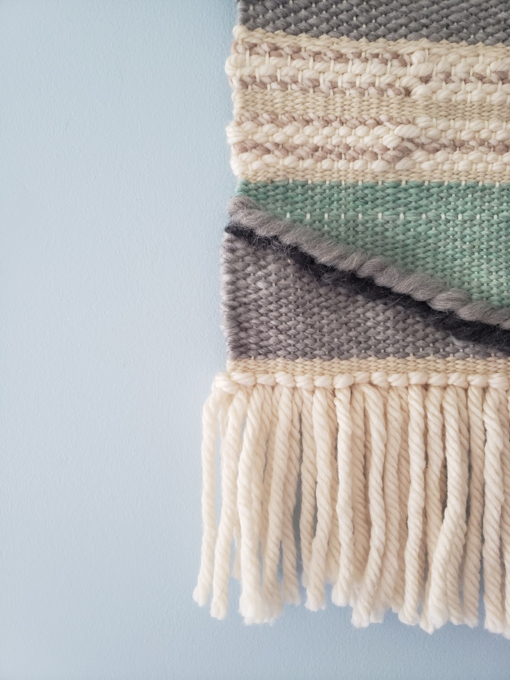 corner of a weaved tapestry in white, grey, and teal against a light blue wall