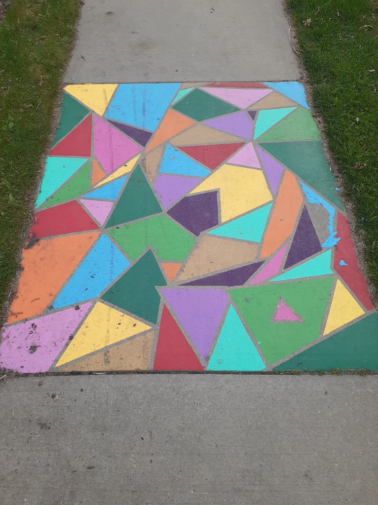 An overhead photo of a sidewalk, surrounded by green grass. The middle section of the sidewalk has been painted with geometric shapes in bright green, orange, pink, purple, blue, yellow, and red.