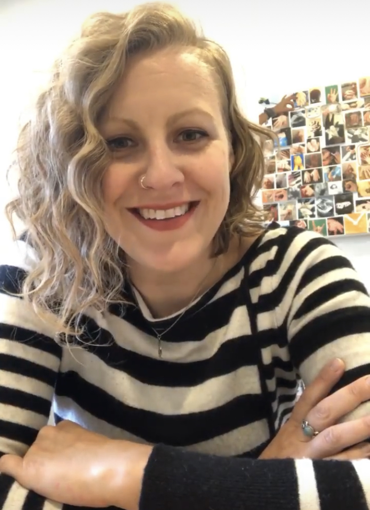 Blonde woman in her 30s smiling, wearing a black and white striped shirt, with a series of photographs behind her.