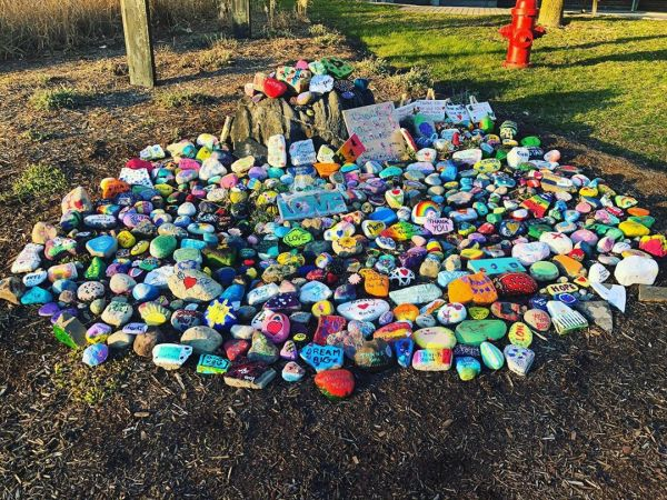 Collection of positivity painted rocks gathered together outside the hospital.