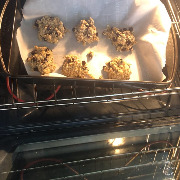 In a baking tray lined with baking paper are six lumps of cookie batter to be baked.