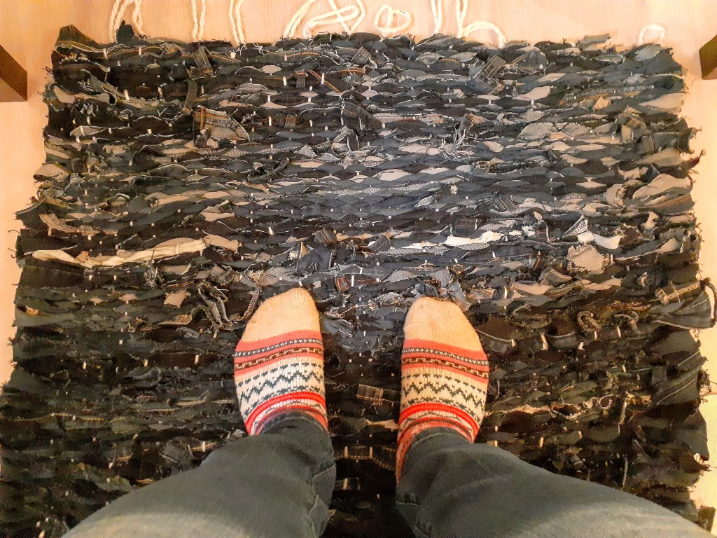 An overhead view of a square rug, made from woven pieces of denim. Tassels of white yarn line the top of the rug. Two feet in colourful pink socks rest on the rug at the bottom of the image.