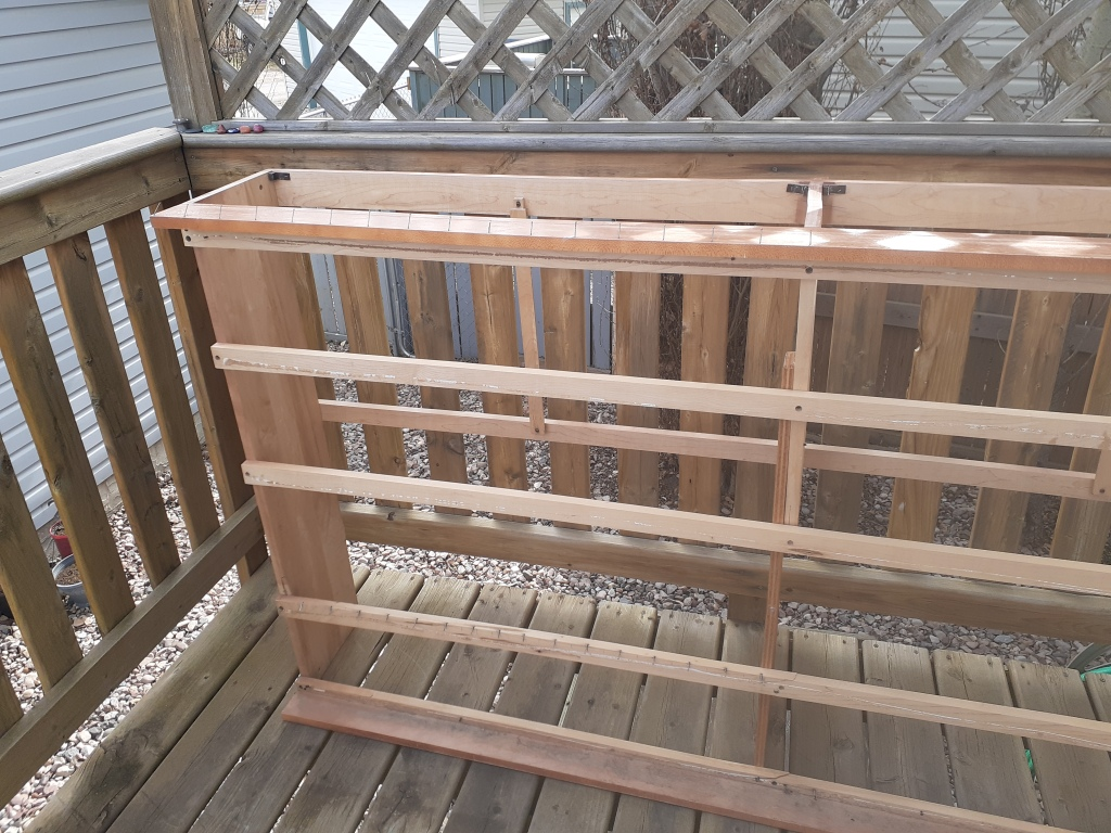 A wooden bedframe turned on its side, which has been repurposed into a loom.