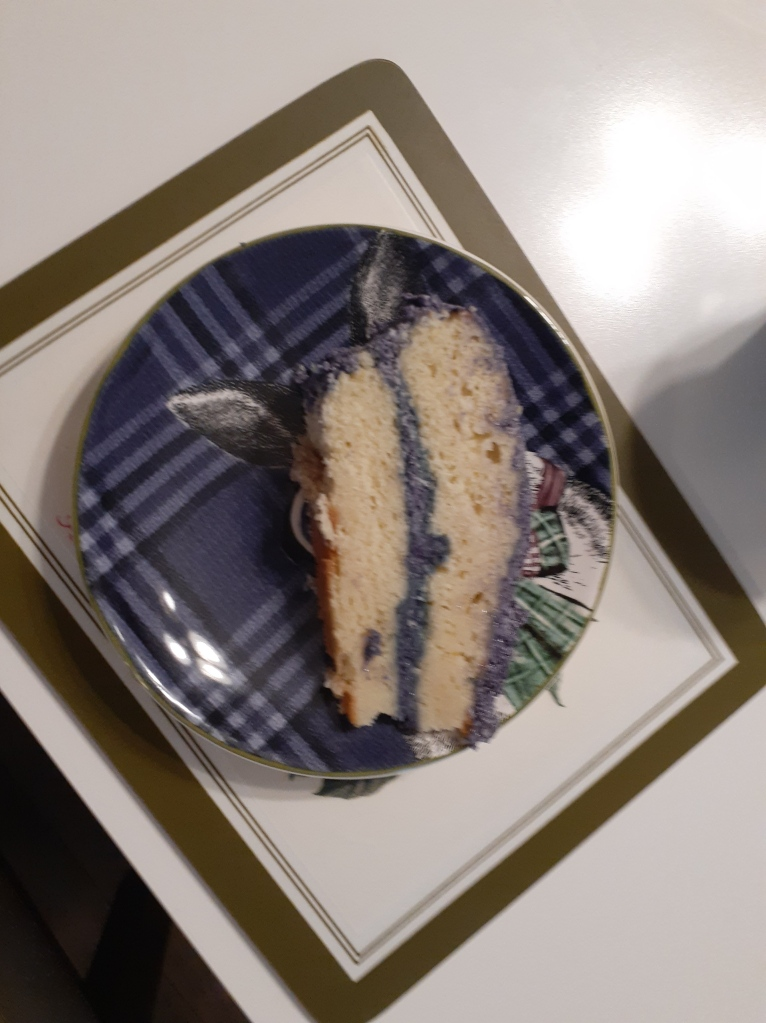 A slice of the same pale yellow cake with purple frosting on a purple plate with a picture of a rabbit.