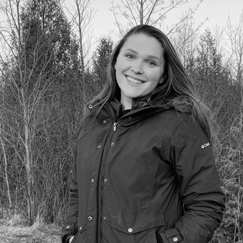Black and white photograph of Sophia Lago standing in front of trees and smiling.