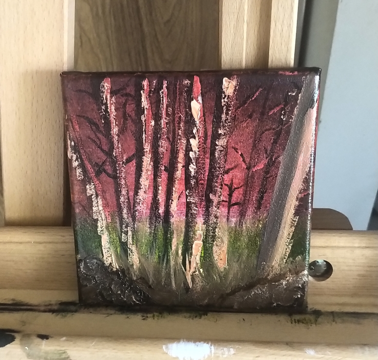 A painted canvas sits on top of an easel. The background of the painting is a sunset, that goes from light pink on the horizon, to darker shades of pink which fades into hues of red and finally shades of dark brown and burgundy at the edges of the canvas. The main focus of the painting are the trees which are scattered throughout. The trees are all similar in size, and have thin trunks and branches. They are dark, reddish-brown in colour and have white highlights. Below the trees is tall, green grass, but as it reaches the foreground, the grass becomes a more muddy, earth-toned green. In the bottom corners of the painting, a dark brown hill with white and lighter brown highlights is shown.