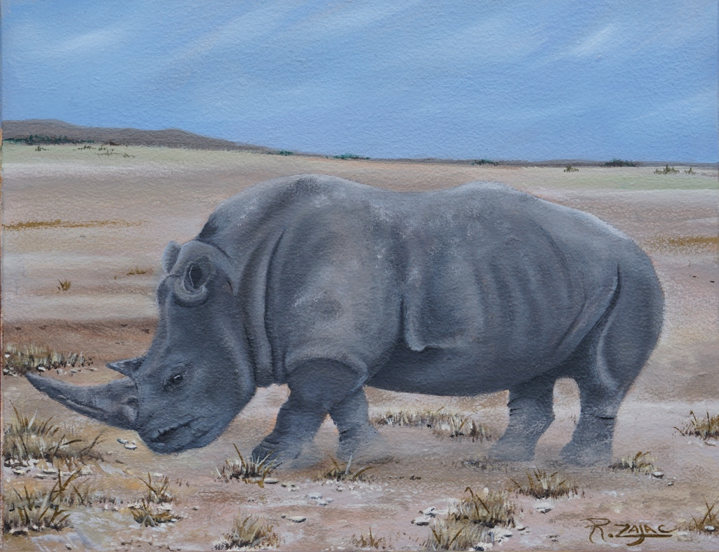 The painting is of a rhino as it grazes. There is a blue sky, brushed with white clouds. The background depicts a beige mountain. Desert shrubs and grass are dispersed throughout the piece. The sand is a beige white color. The Rhino stands in the center foreground.