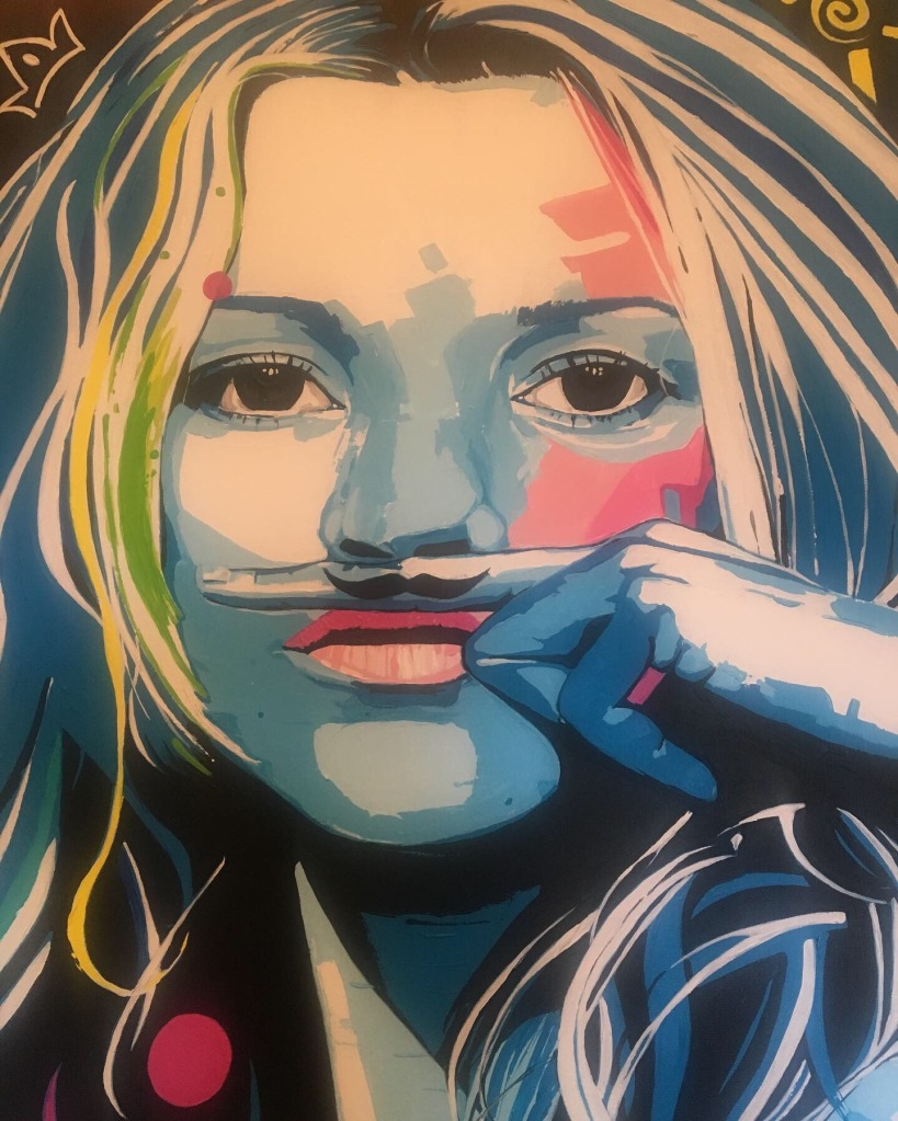 A painting of Kate Moss (white and blue base with splotches of pink, pink lips, and white/blue/green/yellow hair). She is holding up the index finger of her left hand underneath her nose and above her top lip with a black mustache painted on it.