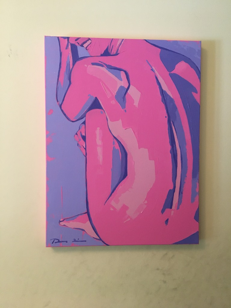 On a beige wall hangs a painting with a purple background and a sitting, crouched, nude, feminine figure painted in pink with purple accents.