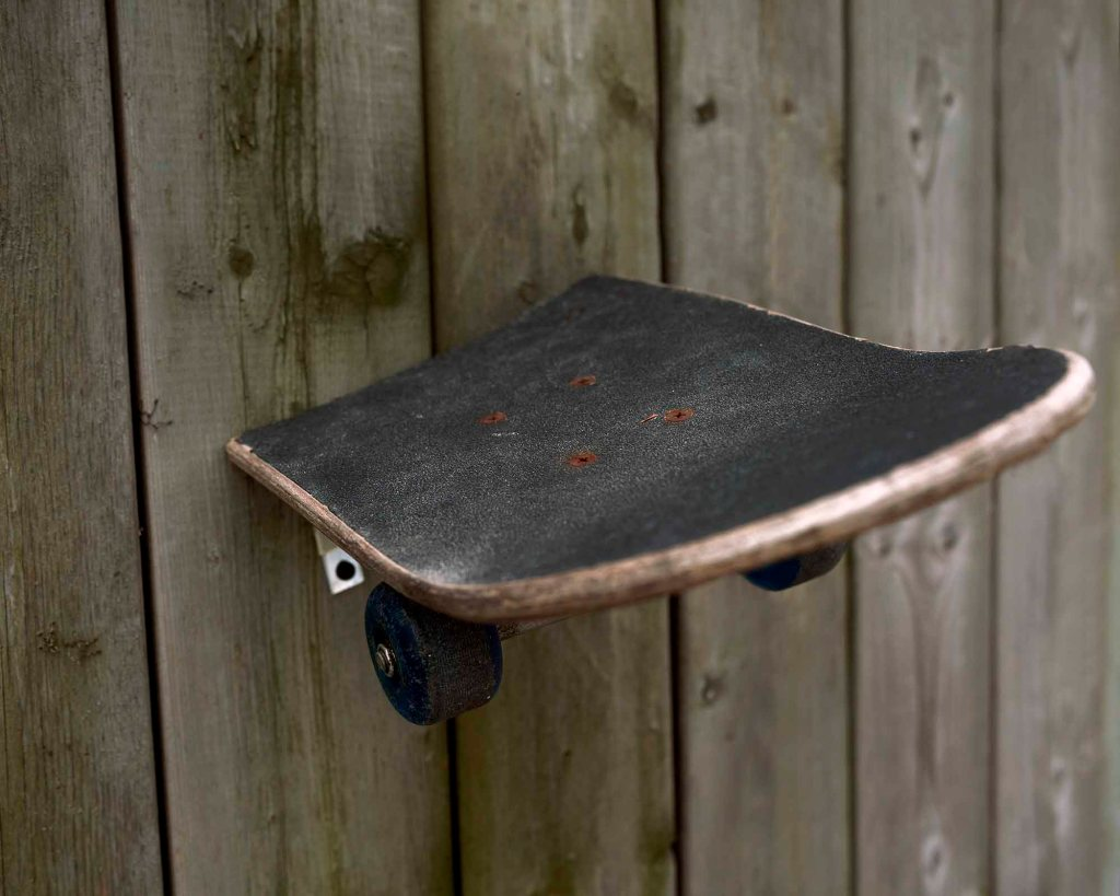 Half of a skateboard portrudes out of a wall that is made up of wooden panels. The skateboard is worn, with its black surface covered in white markings, showing that it is used frequently. The wooden boarder of the skateboard is also worn down, with little chips and dirt covering it. You can also see the skateboard's two, black wheels below the board itself