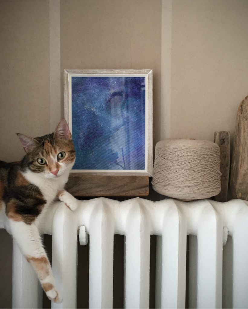 On a white radiator there sits a brown and white cat with a blue painting in a white frame. Also on the radiator is a large spool of twine.